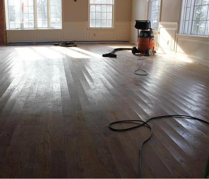 industrial wet/vac removing remaining water from the hardwood floorboards