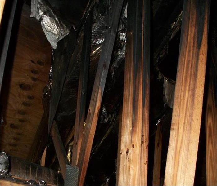 Exposed burned trusses in an attic