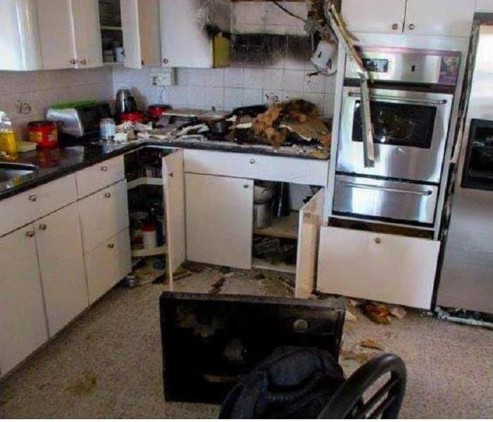burned back wall, no microwave, range top on floor, charred debris on kitchen counters