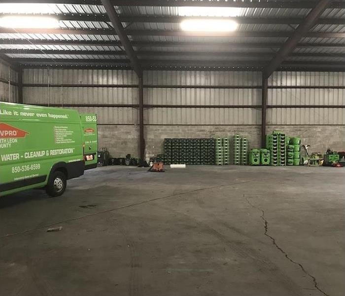 Warehouse with a SERVPRO van and various pieces of equipment stacked against the wall