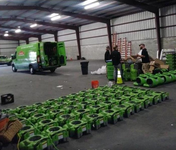 SERVPRO restoration equipment, vehicles, and techs in storage facility